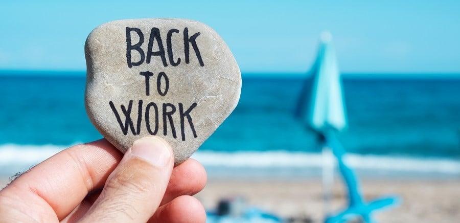 lomalta-paluu-mies-pitelee-kiveä-jossa-lukee-back-to-work