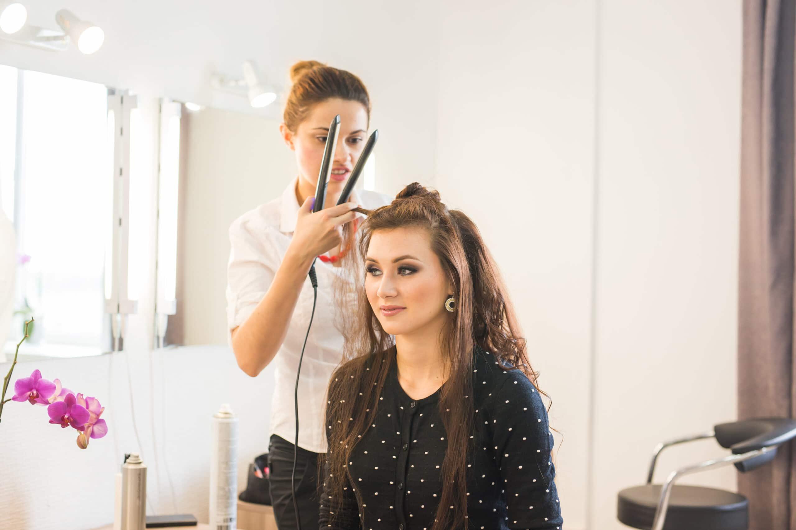 Oudot asiakaspalvelutilanteet. Kampaaja käsittelee asiakkaan hiuksia.
